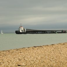 Mystery object, at least 100 ft long, being taken away form the island on a barge?